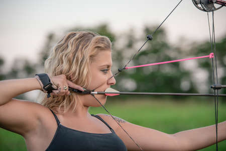 Blonde woman wearing a tanktop aiming a bow and arrow