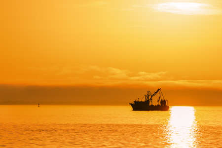 Silhouetted fishing boat on ocean with sunset