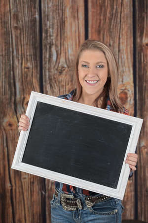 Woman holds up a blank chalk board sign.