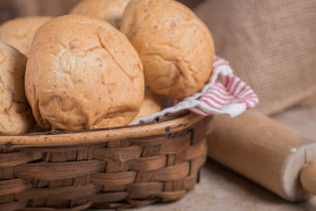 Homemade rolls in a basket with rolling pin in background