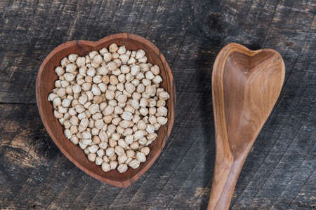 Chick peas in a heart shaped wooden bowl and a wooden spoon Stock Photo