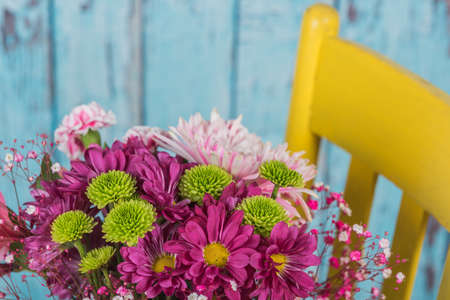 Looking down at a bouquet of flowers in a yellow chair Stock Photo