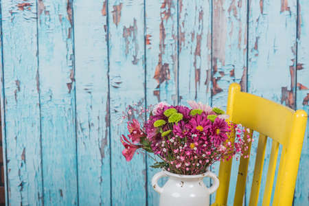 Bouquet of flowers sitting on a yellow chair with rustic wood background