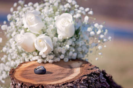 Wedding and engagement ring with black silicone mans ring on wooden stump with white roses in background Stock Photo