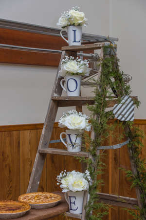 Country wedding decorations on a ladder with love and white roses