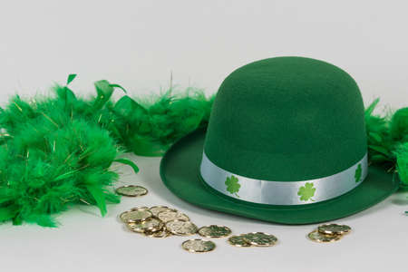 Green felt hat with feather boa and gold coins for St. Patricks Day background