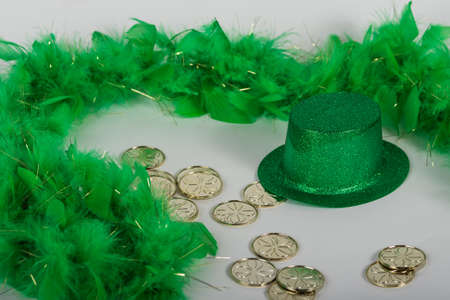 Green glitter hat with feather boa and gold coins for St. Patricks Day background