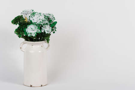 White vintage vase with green and white carnations