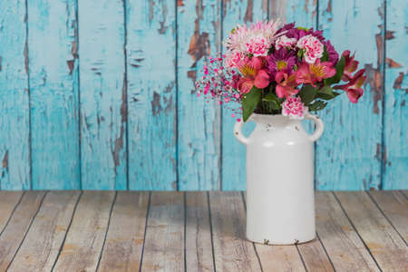 Flowers in a vintage white vase with cracked paint background