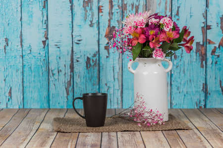 Vintage white vase with flowers and a mug with a peeled paint background