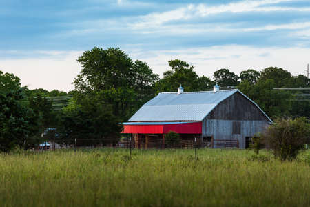 Old wooden barn with red trim  and fences around it