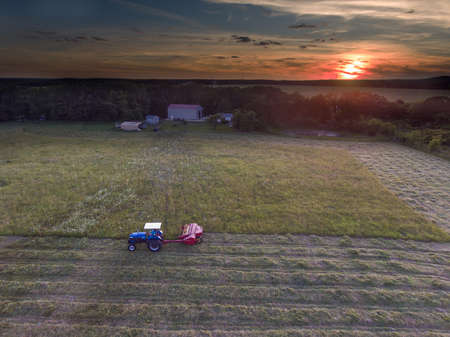 Blue tractor pulling a hay cutter in small field with farm and sunset in background