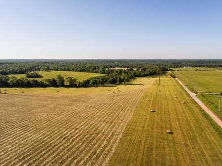 Aerial view of a large field with cut hay and baled hay next to a road Stock Photo