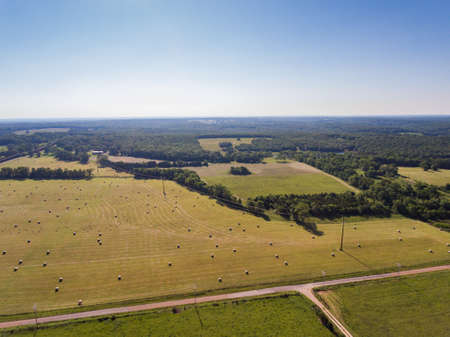 Aerial view of a large hay field and wooded area Stock Photo
