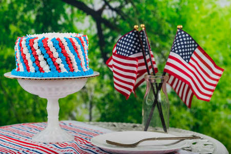 United States of America flags, cake and decor on a table.  Red, white and blue decorations arranged on a table for event Stock Photo