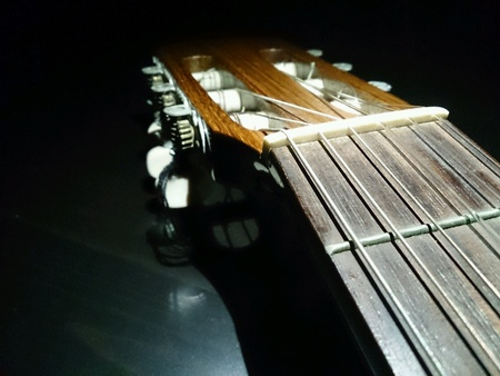 fret: brown acoustic guitar head and top fret against black background