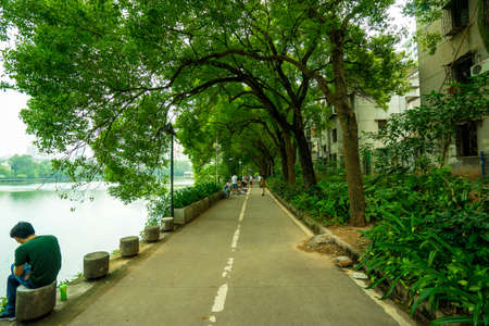 A citizen have a rest in a path by the side of south lake in Huizhou west lake sceinc area, Huizhou, Guangdong, China 新聞圖片