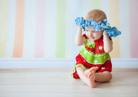 babygirl: Little girl sitting on floor in red dress and blue wreath Stock Photo