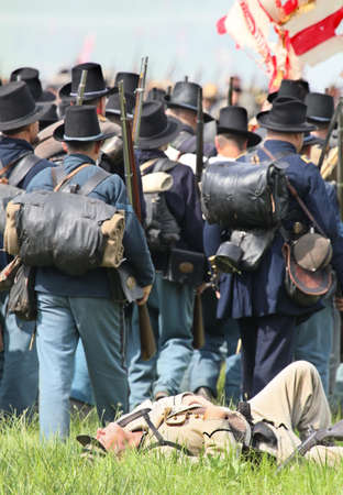 Union Civil War reenactors walk past a fallen Confederate solder at the 150th anniversary of the Battle of Gettysburg, June 28, 2013.