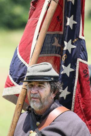 Confederate Civil War reenactor holding the Confederate flag.