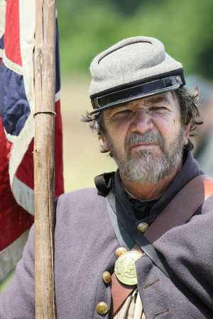 Confederate Civil War reenactor holding the Confederate flag.