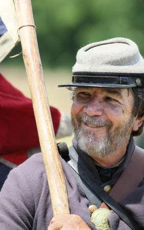 reenactor: Confederate Civil War reenactor holding the Confederate flag.