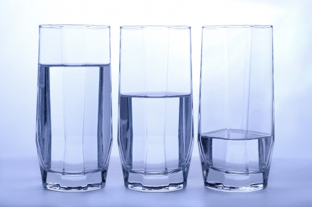 Three glasses of clear water  Full, half and quater photo