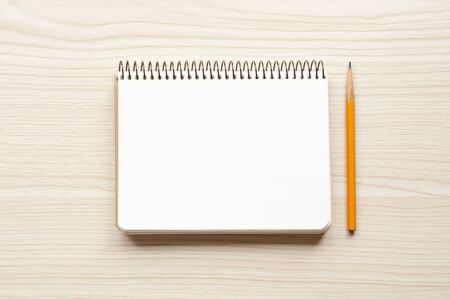 Notepad with blank page and yellow pencil