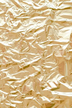Metallic foil texture. Gold, golden background. Metal glittering, crushed, glister surface, backdrop. Crumpled texture. Reflective surface. Folded, rumpled or creased background. Vector illustration