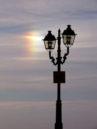 streetlight silhouette against the cloudy sky and sun refraction photo