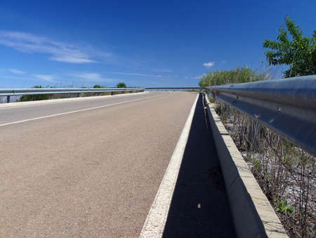 guardrail: empty road with guardrail and blue sky with white clouds
