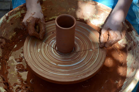 childs  hands making a ceramic pot on the ceramic wheel photo