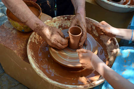 Potters hands directed childs hands, to help to work with the ceramics and creating an earthen jar on the ceramic wheel photo