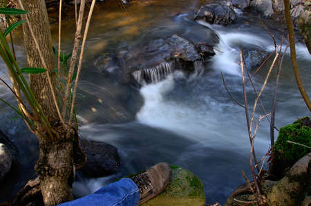 A mountain river flowing through stones and a boot of a hiking  Water is blurred because of streaming, movement and long exposure  photo