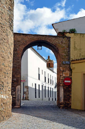 The arc \Arco del Cubo\ (17th century), corresponds to the northern gate outside of the town of Zafra. In the tower is the equestrian statue of Saint James the Moor-slayer and view of tower of the Church of the Candelaria in Zafra, Extremadura, Spai