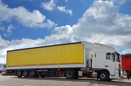 white truck and yellow trailer and sky with white clouds photo