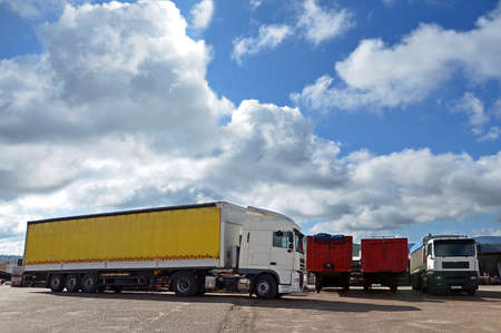 white trucks and yellow and red trailers and sky with white clouds photo