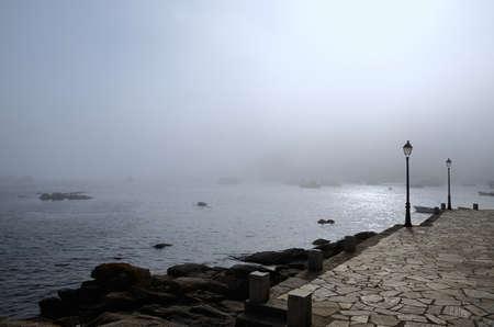 lampposts: paisaje costero con farolas, las rocas y los barcos en la niebla