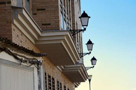 lampposts: fachada de ladrillo con puertas de garaje, ventanas y farolas