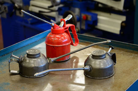 oilcan: detail of  of three oilcans, two gray and a red in a mechanical manufacturing workshop