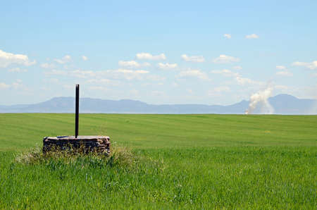 fume: landscape with a water well and mountains and fume in Extremadura, Spain Stock Photo