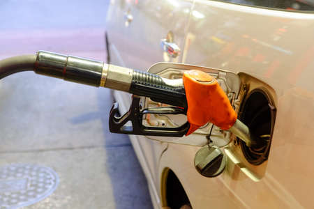 fueling pump: Hands are holding the oil to fill the dispenser with the car. Stock Photo