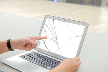 Left finger of woman, she pointing at the white screen laptop, the screen cracked and damaged. Stock Photo