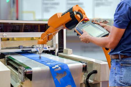 Os engenheiros usam um robô de controle remoto sem fio para segurar uma peça de trabalho da máquina por meio de uma correia transportadora para uma fábrica inteligente, conceito da indústria 4.0