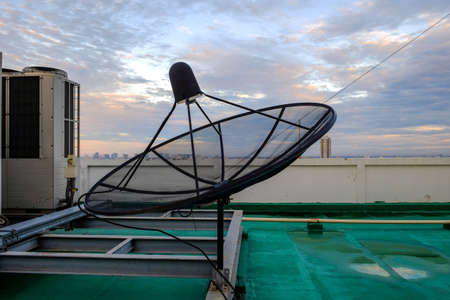 radio unit: Satellite dish receiver and Air Conditioning stand on the rooftop of the building with sunrise sky in the morning