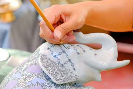 Hands of Thai asian woman  handicraftsman who is using the brush to draw a pattern on the elephant statue finely.