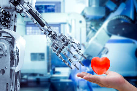 Concept image of human heart on hand send to a robot for make the robots have feelings, love, like a human, on blue tone color machine working blurred background, industry 4.0 and technology concept