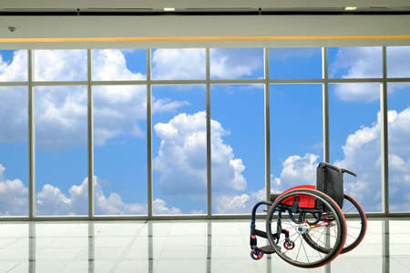 Modern wheelchair parked in empty  room with cloud and sky background, healthcare and medical concept.