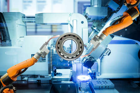 Close-up two robotic welding are working with spherical roller bearing on smart factory, on machine blue tone color background, industry 4.0 and technology. Imagens
