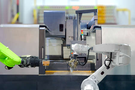 Industrial robotics teamwork on working with CNC lathe machine in smart factory on blurred background, industry 4.0 and technology concept Reklamní fotografie